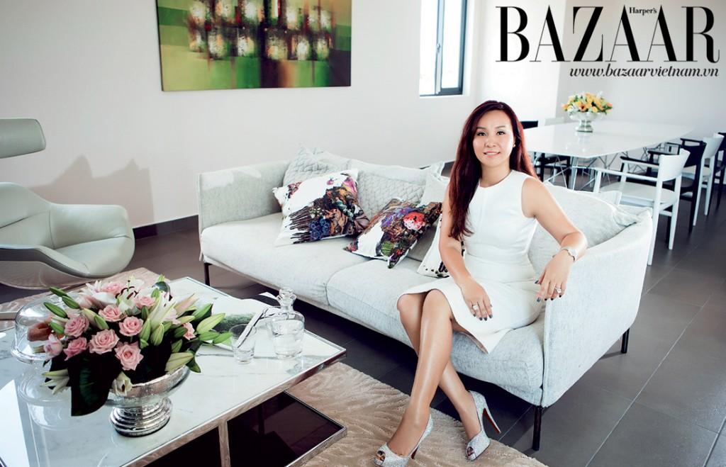 Chị Hà ngồi trong phòng sinh hoạt chung của gia đình. Chị mặc đầm của Michael Kors, đi giày Christian Louboutin