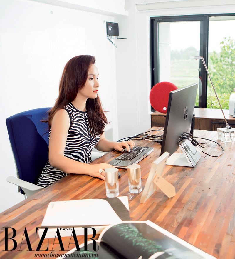 Chị Hà ngồi trong phòng làm việc, mặc đầm Michael Kors