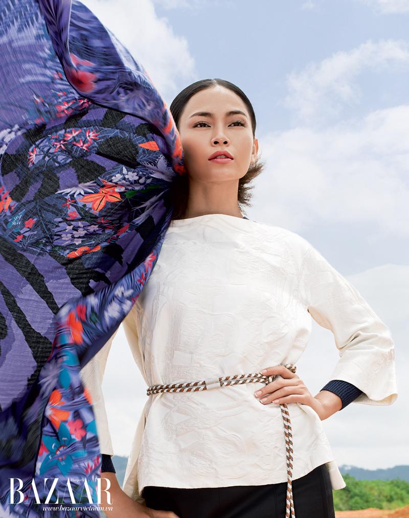 Áo kiểu màu trắng dập nổi họa tiết xẻ hông, thắt lưng dạng dây mảnh, quần tây, khăn lụa khổ lớn buộc trên tóc, Hermès.