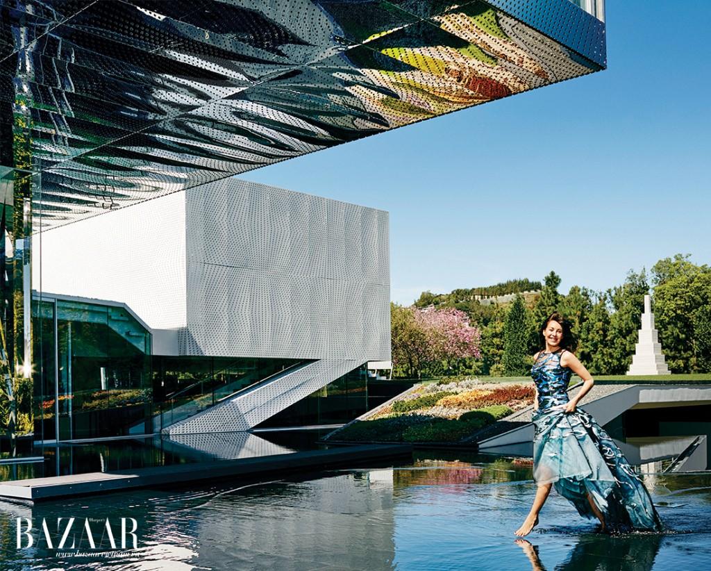 Ngoại cảnh thép không rỉ của căn nhà, được thiết kế bởi kiến trúc sư Michael Maltzan, hứng lấy ánh phản chiếu từ hồ nước bên dưới. Mellon mặc váy Carolina Herrera