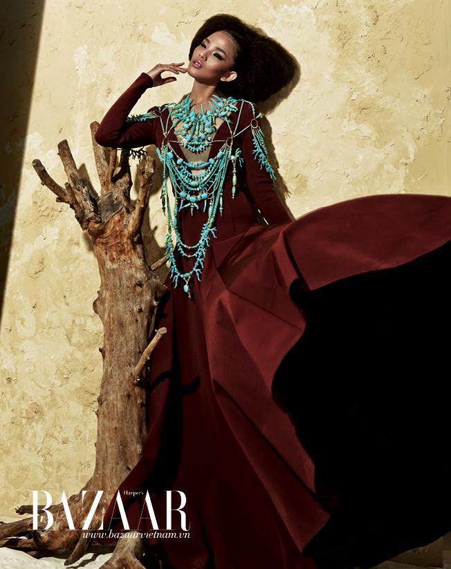 Đầm màu hổ phách với tùng váy xòe rộng, vòng cổ nhiều lớp màu xanh ngọc làm từ xương động vật châu Phi, kết tay cầu kỳ
