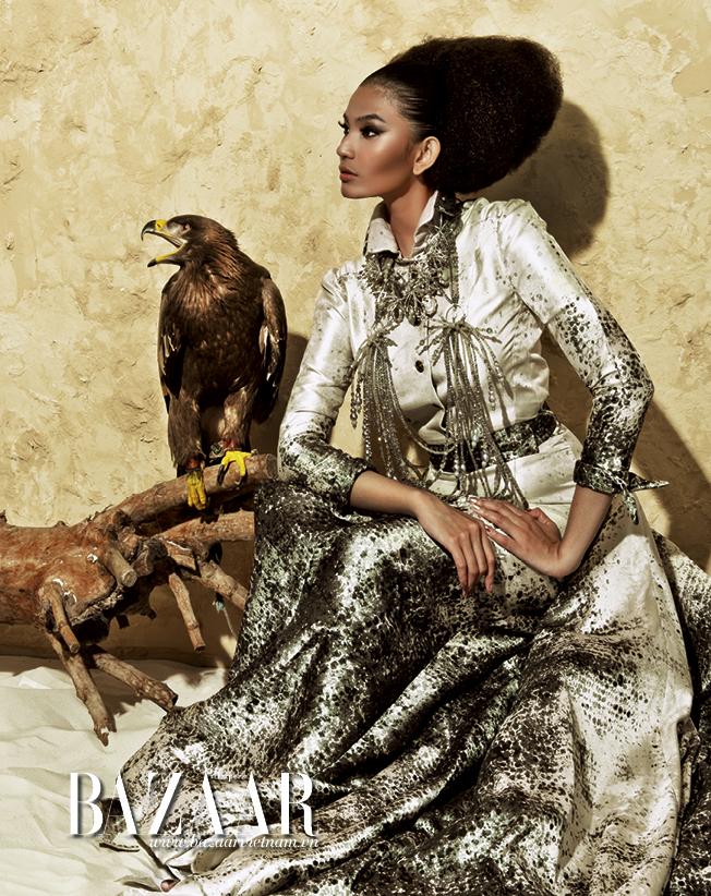 Đầm lụa bóng dạng áo khoác xẻ tà cao, in họa tiết mô phỏng bão cát trên sa mạc Sahara, vòng cổ nhiều tầng đính đá