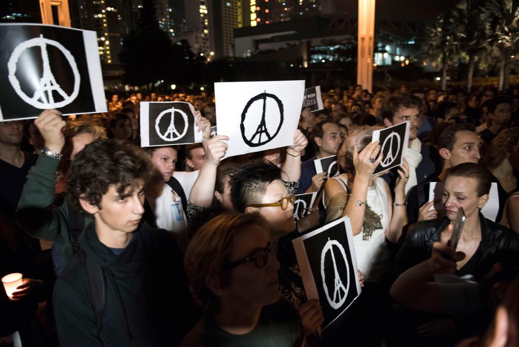 Đám đông giơ cao biểu tượng tại một sự kiện tại Hồng Kông tưởng nhớ nạn nhân của vụ khủng bố ở Paris hôm qua