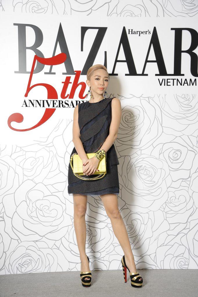 Ca sĩ Tóc Tiên trong chiếc đầm ngắn khoe trọn đôi chân dài. Cô lựa chọn đôi khuyên tai nổi bật cùng chiếc túi vàng Christian Dior