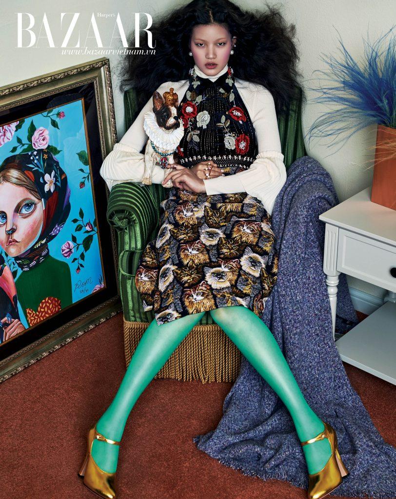 Áo len cổ lọ, Salvatore Ferragamo. Yếm len đen thêu hoa, H&M. Váy in họa tiết mặt mèo, Stella McCartney. Vớ xanh, giày cao gót màu gold, Gucci. Earcuff và nhẫn, CYE Design. Hoa tai đính ngọc trai, Budda&Boomi