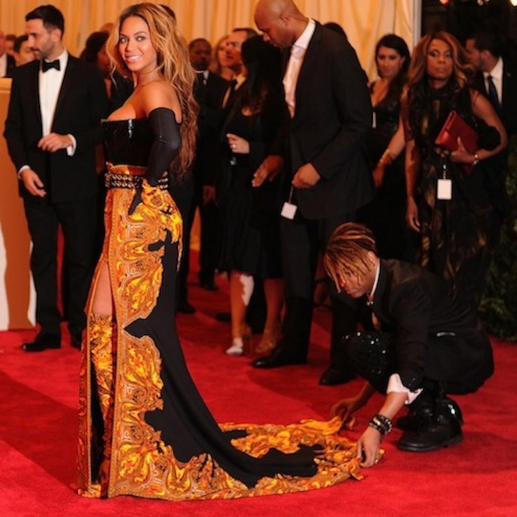 Ca sĩ Beyoncé được stylist Ty Hunter sửa váy trên thảm đỏ.