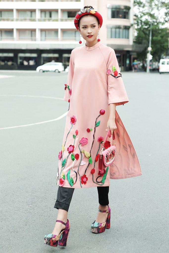 Áo dài cách điệu màu hồng pastel kết hợp cùng quần ôm và phụ kiện mang lại vẻ hiện đại, cá tính