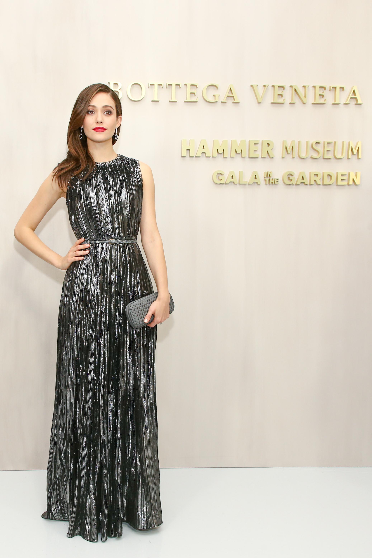 Emmy Rossum rạng ngời với đầm lụa ánh bạc Lurex Jacquard cùng ví cầm tay xám Intrecciato Knot.