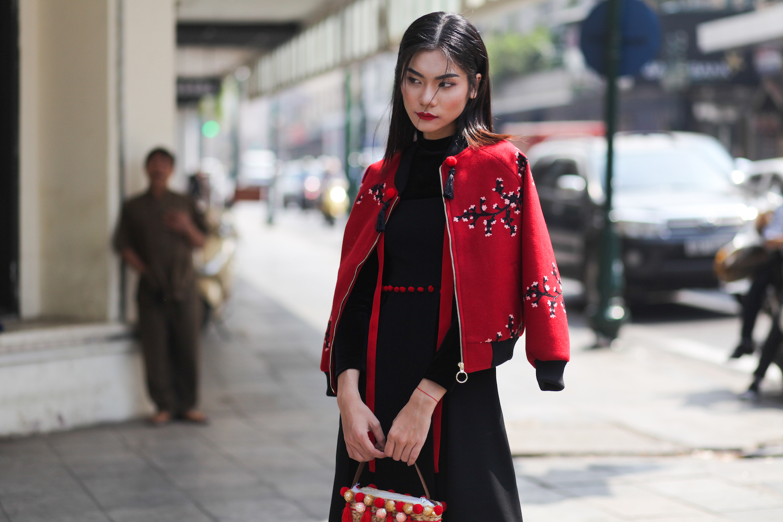 Kim Dung quyến rũ huyền bí khi kết hợp 2 màu đen, đỏ. Chiếc váy đen không hề đơn điệu khi được thêm thắt bởi dây trang trí đỏ tươi thả từ phần cổ và chàng hạt bông gắn quanh eo. Trong tiết trời chớm lạnh, cô nàng chọn thêm một chiếc bomber đỏ trẻ trung thêu hoa đen; cùng với chiếc túi xách len điểm đỏ độc đáo. Tất cả tạo nên một bộ trang phục ton-sur-ton bắt mắt.