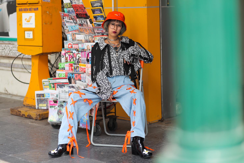 Với áo khoác vằn đen trắng, denim baggy đơn giản được làm mới lại cùng hàng lace-up tông cam; kết hợp cùng chiếc mũ vải cam sáng, bạn nữ đã thực sự thu hút ánh nhìn trên đường phố Hà Nội.