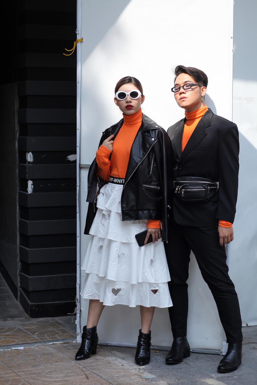 Đôi bạn diện áo turtle neck sành điệu đỏ cam lấp ló bên trong áo khoác da đen.