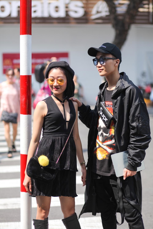 """Bộ đôi """"All black"""" kết hợp đồng điệu; ăn điểm nhờ cặp kính bắt mắt cùng màu với áo phông in hình."""