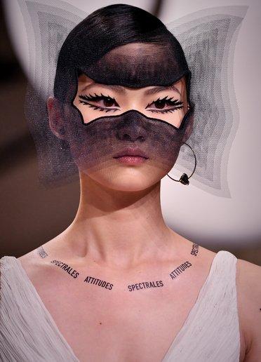 Hình xăm giả trên xương quai xanh của các người mẫu trong show diễn Dior lại là một ẩn dụ nữ quyền khác. Những dòng chữ do nghệ sĩ trang diểm Peter Philips tạo ra được lấy từ các câu nói của nhà thơ và nghệ sĩ siêu thực Pháp André Breton.